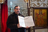 Father Nadim Shakur presents an Arabic bible used in community prayers at the Mi'ilya Church of the Annunciation. Mi'ilya, Israel. 11-Dec-2012. <br /> <br /> Mi'ilya, an Arab village in the Western Galilee, has a population of 3,100 Melkite Christians belonging to the Greek Catholic Church tracing their history to 1st century Christians of Antioch, Turkey, where Christianity was introduced by St. Peter.