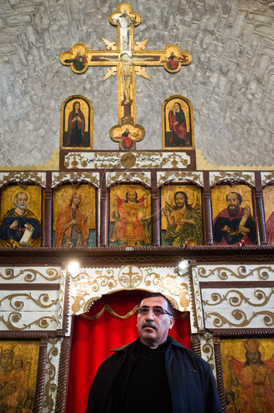 """Father Nadim Shakur presents the Mi'ilya Church of the Annunciation interior showing the """"Templon"""", a decorated covered screen with icons and paintings,  which separates  the hall and the sanctuary behind it. Mi'ilya, Israel. 11-Dec-2012. <br /> <br /> Mi'ilya, an Arab village in the Western Galilee, has a population of 3,100 Melkite Christians belonging to the Greek Catholic Church tracing their history to 1st century Christians of Antioch, Turkey, where Christianity was introduced by St. Peter."""