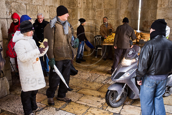 Old City visitors take refuge from the cold and rain in the Jaffa Gate structure. Jerusalem, Israel. 21-Dec-2012.<br /> <br /> A cold, windy and rainy Winter Solstice morning at the Jaffa Gate as locals and tourists seek refuge from the rain rather than Armageddon at end of the Mayan Calendar.