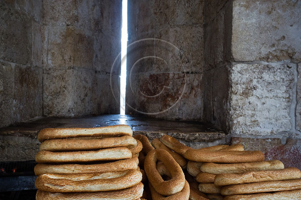 Kaek, local sesame seed covered bagels, are sold from a cart inside the Jaffa Gate structure as sunlight slips in through what once served as a thin embrasure. Jerusalem, Israel. 21-Dec-2012.<br /> <br /> A cold, windy and rainy Winter Solstice morning at the Jaffa Gate as locals and tourists seek refuge from the rain rather than Armageddon at end of the Mayan Calendar.