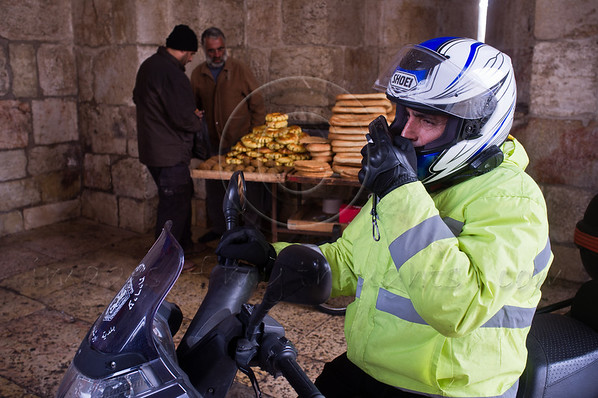 A municipal inspector on a motorbike takes refuge from the cold and rain in the Jaffa Gate structure. Behind him a local kaek vendor sells his merchandise from a cart. Jerusalem, Israel. 21-Dec-2012.<br /> <br /> A cold, windy and rainy Winter Solstice morning at the Jaffa Gate as locals and tourists seek refuge from the rain rather than Armageddon at end of the Mayan Calendar.