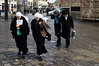 Two Christian nuns and two Jewish Orthodox men lean forward against the wind and rain as they exit the Old City through the Jaffa Gate on the morning of the Winter Solstice, and what some expect to be, the 'end of the world'. Jerusalem, Israel. 21-Dec-2012.<br /> <br /> A cold, windy and rainy Winter Solstice morning at the Jaffa Gate as locals and tourists seek refuge from the rain rather than Armageddon at end of the Mayan Calendar.