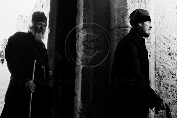 Two unrelated priests with walking sticks enter the Old City through the Jaffa Gate on the morning of the Winter Solstice, and what some expect to be, the 'end of the world'. Jerusalem, Israel. 21-Dec-2012.<br /> <br /> A cold, windy and rainy Winter Solstice morning at the Jaffa Gate as locals and tourists seek refuge from the rain rather than Armageddon at end of the Mayan Calendar.