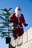 Issa, in a Santa Claus costume, rings his bell and wishes everyone a Merry Christmas as he walks upon the Old City walls at a Christmas tree distribution site near the Jaffa Gate. Jerusalem, Israel. 23-Dec-2012.<br /> <br /> The Keren Kayemeth LeIsrael - Jewish National Fund, and the Jerusalem Municipality, assisted by Issa dressed as Santa Claus, distribute specially grown Arizona Cypress trees as Christmas trees to the Christian population at the Jaffa Gate.