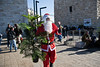 Issa, in a Santa Claus costume, rings his bell and wishes everyone a Merry Christmas at a Christmas tree distribution site at the Jaffa Gate. Jerusalem, Israel. 23-Dec-2012.<br /> <br /> The Keren Kayemeth LeIsrael - Jewish National Fund, and the Jerusalem Municipality, assisted by Issa dressed as Santa Claus, distribute specially grown Arizona Cypress trees as Christmas trees to the Christian population at the Jaffa Gate.