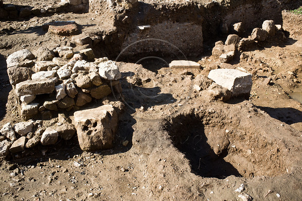 """The square structure of an altar (L), in what would have been the temple courtyard, stands by a pit (R) in which archaeologists found skeletal remains of sheep, goats, cattle and deer - all kosher animals and allowed for consumption in Judaism. Motza, Israel. 26-Dec-2012.<br /> <br /> A temple, pottery figurines and other artifacts, providing rare testimony of a ritual cult in the Jerusalem region at the beginning of the Monarchy Period, uncovered in excavations by the Israel Antiquities Authority at Tel Motza.<br /> <br /> Excerpt from Israel Antiquities Authority press release, 26-Dec-2012:<br /> Rare evidence of the religious practices and rituals in the early days of the Kingdom of Judah has recently been discovered at Tel Motza, to the west of Jerusalem. In excavations the Israel Antiquities Authority is currently conducting at the Tel Motza archaeological site, prior to work being carried out on the new Highway 1 from Sha'ar HaGai to Jerusalem by the National Roads Company (previously the Public Works Department), a ritual building (a temple) and a cache of sacred vessels some 2,750 years old have been uncovered.<br /> According to Anna Eirikh, Dr. Hamoudi Khalaily and Shua Kisilevitz, directors of the excavation on behalf of the Israel Antiquities Authority, """"The ritual building at Tel Motza is an unusual and striking find, in light of the fact that there are hardly any remains of ritual buildings of the period in Judea at the time of the First Temple. The uniqueness of the structure is even more remarkable because of the vicinity of the site's proximity to the capital city of Jerusalem, which acted as the Kingdom's main sacred center at the time."""" According to the archaeologists, """"Among other finds, the site has yielded pottery figurines of men, one of them bearded, whose significance is still unknown.""""<br /> Tel Motza and the surrounding region are renowned for their prime archaeological importance. Many finds have previously been uncovered at the site, fro"""