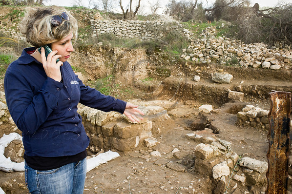 """Archaeologist Anna Eirikh stands at the entrance to the temple, discovered at Tel-Motza. Eirikh's left hand is positioned just above the east-facing entrance, conforming to the tradition of temple construction in the ancient Near East. Motza, Israel. 26-Dec-2012.<br /> <br /> A temple, pottery figurines and other artifacts, providing rare testimony of a ritual cult in the Jerusalem region at the beginning of the Monarchy Period, uncovered in excavations by the Israel Antiquities Authority at Tel Motza.<br /> <br /> Excerpt from Israel Antiquities Authority press release, 26-Dec-2012:<br /> Rare evidence of the religious practices and rituals in the early days of the Kingdom of Judah has recently been discovered at Tel Motza, to the west of Jerusalem. In excavations the Israel Antiquities Authority is currently conducting at the Tel Motza archaeological site, prior to work being carried out on the new Highway 1 from Sha'ar HaGai to Jerusalem by the National Roads Company (previously the Public Works Department), a ritual building (a temple) and a cache of sacred vessels some 2,750 years old have been uncovered.<br /> According to Anna Eirikh, Dr. Hamoudi Khalaily and Shua Kisilevitz, directors of the excavation on behalf of the Israel Antiquities Authority, """"The ritual building at Tel Motza is an unusual and striking find, in light of the fact that there are hardly any remains of ritual buildings of the period in Judea at the time of the First Temple. The uniqueness of the structure is even more remarkable because of the vicinity of the site's proximity to the capital city of Jerusalem, which acted as the Kingdom's main sacred center at the time."""" According to the archaeologists, """"Among other finds, the site has yielded pottery figurines of men, one of them bearded, whose significance is still unknown.""""<br /> Tel Motza and the surrounding region are renowned for their prime archaeological importance. Many finds have previously been uncovered at the site, from a varie"""