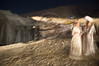 Two Israeli Opera Carmen performers approach the stage from the wardrobe area for full dress rehearsal in a desert background. Photo shot in slow shutter speed creates an impressionist feeling. Massada, Israel. 6-June-2012.
