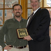 Chadron State College President Randy Rhine presents Justin Haag, outgoing marketing coordinator, with a plaque commemorating his 12 years of service to the college. (Photo by Daniel Binkard/Chadron State College)