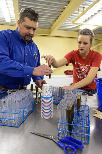 Chadron State College student Kara Sutphen, right, hands a bovine fecal sample to John Denton, senior territory manager for Merck Animal Health. Denton and Dr. Donald H. Bliss, veterinary parasitologist, worked with Sutphen to study parasite egg counts in area cattle. Sutphen is a sophomore from Lakeside who teamed up with Mara Seifer, a junior from Tryon. The students plan to submit their research to beef producer publications. (Photo by Daniel Binkard/Chadron State College)