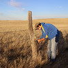 Chadron State College student Josh Larson attaches a trail camera to a fence post northeast of Harrison in late October 2013 as part of the swift fox study.