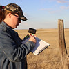 Katie Whalen from Alladin, Wyo., prepares a whiteboard indicating the number and location of a trail camera northeast of Harrison as part of a collaborative study of the endangered swift fox involving CSC, UNL and the Nebraska Game and Parks Commission.