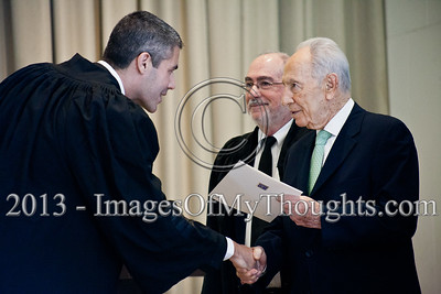 President of the State of Israel, Shimon Peres, shakes the hand of Advocate Ohad Gordon and hands him a letter of appointment as a Magistrate Court judge in the Jerusalem District. Jerusalem, Israel. 14-Jan-2013.  President Shimon Peres grants letters of appointment to twelve new judges at the Presidents' Residence in the presence of Justice Minister Ya'akov Ne'eman and the Honorable Asher Grunis, President of the Supreme Court and High Court of Justice.