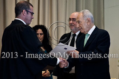 President of the State of Israel, Shimon Peres, shakes the hand of Advocate Shmuel Melamed and hands him a letter of appointment as a Magistrate Court judge in the Tel-Aviv District. Jerusalem, Israel. 14-Jan-2013.  President Shimon Peres grants letters of appointment to twelve new judges at the Presidents' Residence in the presence of Justice Minister Ya'akov Ne'eman and the Honorable Asher Grunis, President of the Supreme Court and High Court of Justice.