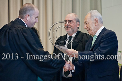 President of the State of Israel, Shimon Peres, shakes the hand of Advocate Tal Peperani and hands him a letter of appointment as a Magistrate Family Court judge in the Haifa District. Jerusalem, Israel. 14-Jan-2013.  President Shimon Peres grants letters of appointment to twelve new judges at the Presidents' Residence in the presence of Justice Minister Ya'akov Ne'eman and the Honorable Asher Grunis, President of the Supreme Court and High Court of Justice.