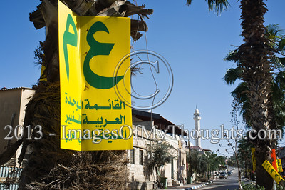 "The main street in Kfar Kassem leading to one of the mosques in the distance is decorated with signs of the United Arab List (Ra'am Ta'al) just one week ahead of Israeli national elections. Kfar Kassem, Israel. 15-Jan-2013.  MK Ibrahim Sarsour, Chairman of the United Arab List (Ra'am Ta'al) and Deputy Chairman of the WAQF, running for reelection for his third term in the Knesset, briefs the press in his Parliamentary Bureau.   Arab-Israelis make up about 20 percent of Israel's population. Some 800,000 have the right to vote in the upcoming Knesset elections (January 22nd); with voter turnout declining across all sectors of Israel society, some analysts are expecting a drop in participation among Muslim, Christian and other Arab-Israeli citizens (or ""Palestinians in Israel"" as some call themselves today).     Professor Asa'd Ghanem reported in a recent press briefing, one third of Arabs who participated in a recent Haifa University poll described themselves as apathetic and rarely voting in national elections while another third said they don't vote at all.  This election season has already been marked by rancorous debate among Arab leaders in Israel, and a general dissatisfaction expressed by Arab citizens with their communal leaders."