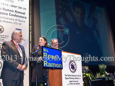 "Ms. Rona Ramon (center), widow of Columbia STS-107 astronaut, Ilan Ramon, addresses the eighth annual Ilan Ramon International Space Conference announcing ""I am proud"", as a photo of her husband is projected behind her. Hertzeliya, Israel. 29-Jan-2013.  Eighth Annual Ilan Ramon International Space Conference convenes commemorating a decade to Columbia Mission STS-107 with senior representatives of 14 space agencies including NASA Administrator and astronauts from the US, Japan, Russia and Kazakhstan."