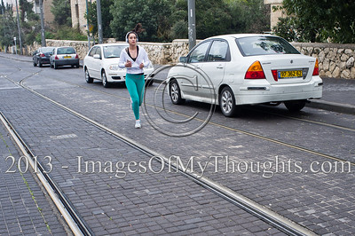 A young woman jogs along the Jerusalem tram tracks listening to music through earphones on a Saturday morning. Jerusalem, Israel. 2-Feb-2013.   Norms formed during the British Mandate dictating a status quo in regard to observance of the Sabbath, later formulated in the 1951 legislation forbidding employment of Jews on the Sabbath, suspend public transportation almost nationwide.