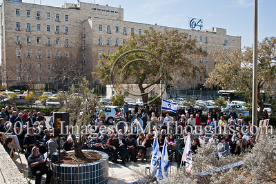 "Participants of a 1983 pro-peace demonstration and followers take part in a 30-year commemoration ceremony for murdered activist Emil Grunzweig near the PM's Office (background). Jerusalem, Israel. 10-Feb-2013.  ""Peace Now"" leads a 30-year commemoration ceremony for activist Emil Grunzweig, murdered in 1983 by a grenade thrown by right-wing activist Yona Avrushmi at demonstrators calling for the resignation of Defense Minister Ariel Sharon."