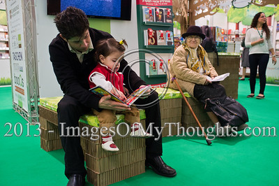 A man reads a children's book to a young girl at the Jerusalem International Book Fair. Jerusalem, Israel. 10-Feb-2013.  First held in 1963, the Jerusalem International Book Fair is a unique biennial event, business fair and a prestigious and important cultural event. 600 publishers and authors from more than 30 countries display more than 100,000 books.