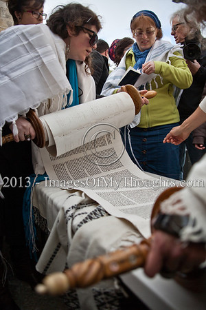Women's hands wrapped in phylacteries handle a Torah scroll in a manner totally impermissible in Orthodox Judaism as Women of the Wall continue their month of Adar celebration in a prayer service and Torah reading near the Kishle police station. Jerusalem, Israel. 11-Feb-2013.  Morning prayers celebrating the month of Adar were conducted today on the women's side of the Kotel by Women of The Wall, in defiance of rulings forbidding them to pray in the manner of orthodox men. Ten were detained by police for questioning.