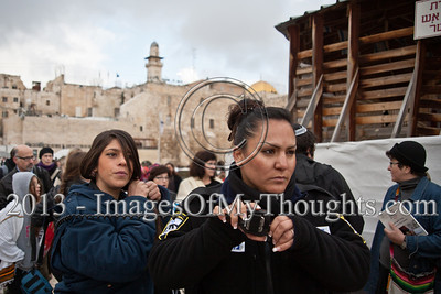 A policewoman escorts Women of The Wall out of the Western Wall plaza communicating to coordinate arrests of several worshippers. Jerusalem, Israel. 11-Feb-2013.  Morning prayers celebrating the month of Adar were conducted today on the women's side of the Kotel by Women of The Wall, in defiance of rulings forbidding them to pray in the manner of orthodox men. Ten were detained by police for questioning.