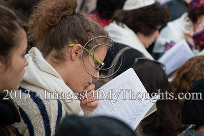 A woman praying with Women of The Wall, celebrating the month of Adar, reads from a prayer book at the Kotel while wearing a Talit prayer shawl in the custom of men. Jerusalem, Israel. 11-Feb-2013.  Morning prayers celebrating the month of Adar were conducted today on the women's side of the Kotel by Women of The Wall, in defiance of rulings forbidding them to pray in the manner of orthodox men. Ten were detained by police for questioning.