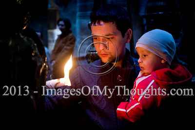 A man holds a candle and his infant child by the Edicule of the Tomb in the Church of The Holy Sepulchre on Ash Wednesday. Jerusalem, Israel. 13-Feb-2013.  Christian pilgrims flock the Church of The Holy Sepulchre on Ash Wednesday, the first day of Lent, 46 days before Easter. The Church of The Holy Sepulchre preserves the most important moments of the death and resurrection of Jesus Christ.