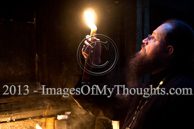 A priest holds a candle and looks up at the Edicule of the Tomb in the Church of The Holy Sepulchre on Ash Wednesday. Jerusalem, Israel. 13-Feb-2013.  Christian pilgrims flock the Church of The Holy Sepulchre on Ash Wednesday, the first day of Lent, 46 days before Easter. The Church of The Holy Sepulchre preserves the most important moments of the death and resurrection of Jesus Christ.