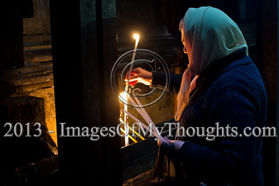 A woman prays silently holding a candle by the Edicule of the Tomb as thousands of Christian pilgrims and believers flock the Church of The Holy Sepulchre on Ash Wednesday. Jerusalem, Israel. 13-Feb-2013.  Christian pilgrims flock the Church of The Holy Sepulchre on Ash Wednesday, the first day of Lent, 46 days before Easter. The Church of The Holy Sepulchre preserves the most important moments of the death and resurrection of Jesus Christ. Jerusalem, Israel. 13-Feb-2013.