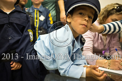 A young boy, dressed up for Purim as policemen, waits to enter the Israel Police Commissioner's meeting room and meet Commissioner Yohanan Danino. Jerusalem, Israel. 25-Feb-2013.  Children of policemen, in Purim police costumes, man the positions of the Israel Police High Command at the National HQ. Purim, one of Judaism's more colorful holidays, commemorates the miraculous salvation of the Jews from a Persian genocidal plot.