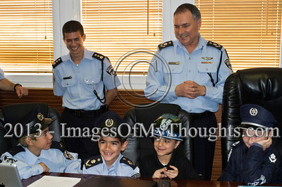 Israel Police Commissioner Yohanan Danino (rear right) is in high spirits as he hosts the children of serving policemen in the Israel Police National Headquarters High Command meeting room. Jerusalem, Israel. 25-Feb-2013.  Children of policemen, in Purim police costumes, man the positions of the Israel Police High Command at the National HQ. Purim, one of Judaism's more colorful holidays, commemorates the miraculous salvation of the Jews from a Persian genocidal plot.
