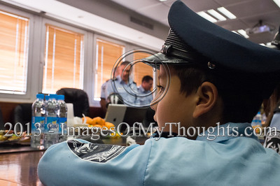 A young boy, dressed up for Purim as policemen, sits in the Israel Police Commissioner's meeting room as Commissioner Yohanan Danino looks on in the background. Jerusalem, Israel. 25-Feb-2013.  Children of policemen, in Purim police costumes, man the positions of the Israel Police High Command at the National HQ. Purim, one of Judaism's more colorful holidays, commemorates the miraculous salvation of the Jews from a Persian genocidal plot.