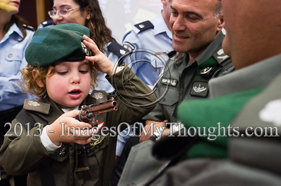 A young boy is dressed up for Purim as a Border Policeman besides his father, a serving Border Policeman, in the Israel Police National Headquarters High Command meeting room. Jerusalem, Israel. 25-Feb-2013.  Children of policemen, in Purim police costumes, man the positions of the Israel Police High Command at the National HQ. Purim, one of Judaism's more colorful holidays, commemorates the miraculous salvation of the Jews from a Persian genocidal plot.