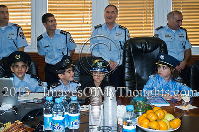 Israel Police Commissioner Yohanan Danino (rear center) is in high spirits as he hosts the children of serving policemen in the Israel Police National Headquarters High Command meeting room. Jerusalem, Israel. 25-Feb-2013.  Children of policemen, in Purim police costumes, man the positions of the Israel Police High Command at the National HQ. Purim, one of Judaism's more colorful holidays, commemorates the miraculous salvation of the Jews from a Persian genocidal plot.