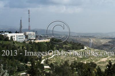 A view to the east from Mount Scopus reveals an Israeli military base (left) overlooking the Palestinian neighborhood of Anata and the course of the security barrier which practically defines a non-existing border. Jerusalem, Israel. 4-March-2013.  E1 area is an obstacle to be overcome in any future peace accord between Israel and the Palestinians. E1 may either determine a continuous Israeli population between Jerusalem and Maale Adumim or a contiguous Palestinian state from North to South.