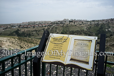 A plaque indicates location of a cornerstone set for future construction of the Mevaseret Adumim neighborhood in 2009. Construction is since frozen in E1 under international pressure. Maale Adumim is visible in the background. Mevaseret Adumim, Israel. 4-March-2013.  E1 area is an obstacle to be overcome in any future peace accord between Israel and the Palestinians. E1 may either determine a continuous Israeli population between Jerusalem and Maale Adumim or a contiguous Palestinian state from North to South.