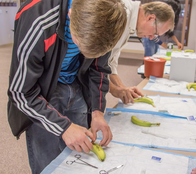 J.T. Engberg of Hastings, Nebraska, left,practices suturing a banana during Chadron State College's Health Professions Showcase Wednesday, Oct. 7, 2015. (Tena L. Cook/Chadron State College)