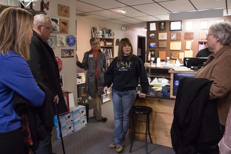 """Shellie Cope, owner of Engravers, center, speaks with representatives of the Nebraska Business Development Center in Chadron and Omaha and the University of Omaha Tuesday, Nov. 29, 2016, during a """"Get to Know You"""" NBDC tour of client businesses. (Photo by Tena L. Cook/Chadron State College)"""