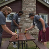 Chadron State College football team members, from left, Anthony Valdez of Cheyenne, Wyo., Alonzo Neal of Aurora, Colo., and Travis Romsa of Burns, Wyo., paint picnic tables at Chadron State Park April 23, 2016, during The Big Event. (Tena L. Cook/Chadron State College)