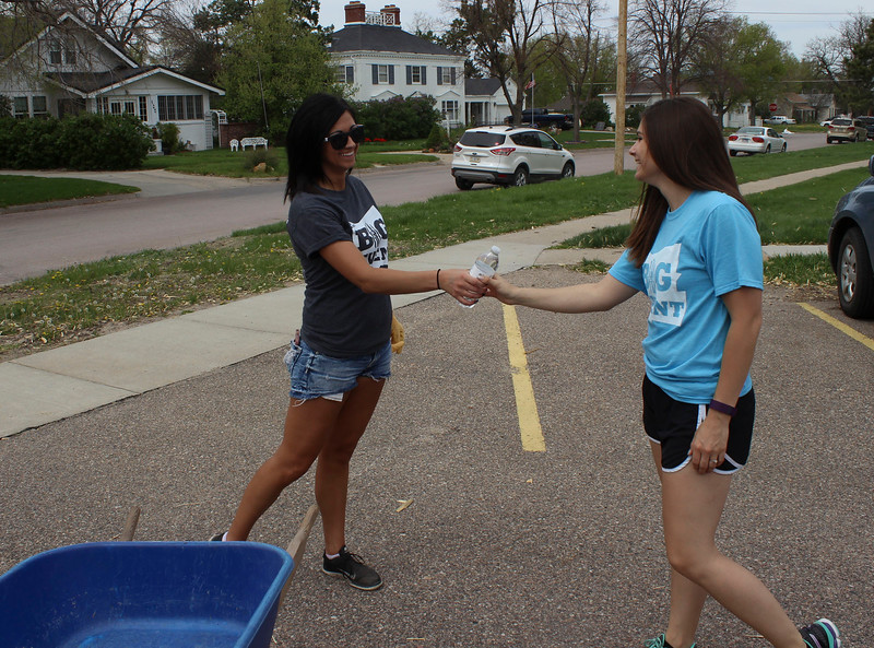 Shelby Dunker of Akron, Colo., left, receives water from Jessica Orose, right, of Piedmont, S.D., at Dawes County Court House Saturday, April 23, 2016, as part of the annual community service project, The Big Event.  (Photo by Conor Casey/CSC)