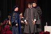 Charith Kapukotuwa is hooded by Dr. Rick Koza while Dr. Joel Hyer looks on during the Chadron State College graduate commencement in Memorial Hall Friday, Dec. 16, 2016. (Photo by Tena L. Cook/Chadron State College)