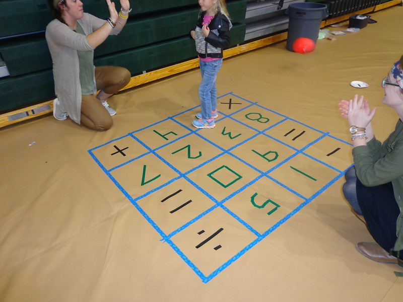 Chadron State College students Katie O'Boyle of Gering, Nebraska, left, and Bailey Broderick of Rapid City, South Dakota, right, play square dance with Olivia Dahlgren during Family Math Night in Hay Springs, Nebraska, in 2014. (Courtesy photo)