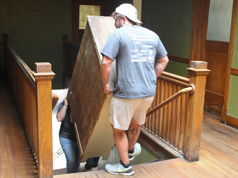 Derek Pollock of Ainsworth, Neb., and Kris Boardman of Gordon, Neb., help carry furniture to the upper level of the Bean Broker as part of Chadron State College's annual community service day, The Big Event. (Photo by Conor Casey/CSC)