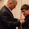 Dr. Randy Rhine, president of Chadron State College, pins a boutonniere  on royalty court attendant Curtis Stevens of St. Paul, Nebraska, in the CSC Student Center Ballroom Oct. 5, 2016. (Photo by Conor Casey/CSC)