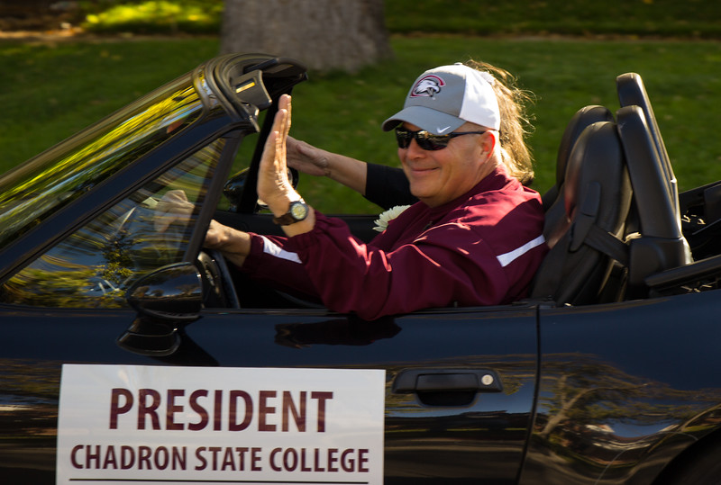 Dr. Randy Rhine, president of Chadron State College, waves to onlookers as he and his wife, Ann, drive down Main Street during CSC's 2016 Homecoming Parade , Oct. 2, 2016.  (Photo by Conor Casey/CSC)