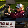 Dr. Randy Rhine, president of Chadron State College, waves to onlookers as he and his wife, Ann, make their way down Main Street during CSC's 2016 Homecoming Parade , Oct. 2, 2016.  (Photo by Conor Casey/CSC)