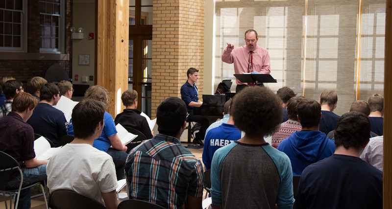 Dr. Joel Schreuder, Chadron State College music faculty member, leads vocalists who took part in Men's Choir Day in the Mari Sandoz Chicoine Atrium Oct. 20, 2016.  (Photo by Conor Casey/Chadron State College)