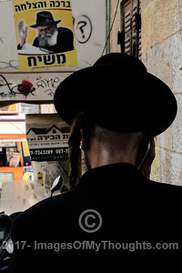 An ultra-Orthodox Jewish man stands below a sign depicting Rabbi Menachem Mendel Schneerson (1902-1994) of the Chabad Lubavitz Orthodox Jewish, Hasidic movement.