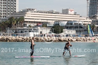 Men practice SAP sailing at Gordon Beach in Tel Aviv